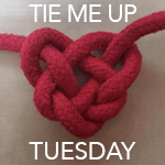"""Badge: A decorative red knot with """"Tie me up Tues"""" written over it."""